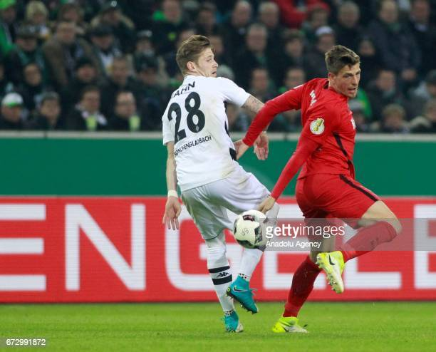 Andre Hahn of Borussia Monchengladbach in action against Bastian Oczipka of Eintracht Frankfurt during the DFB Cup semifinal soccer match between...