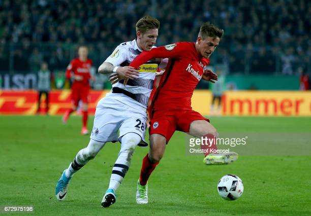 Andre Hahn of Moenchengladbach and Bastian Oczipka of Frankfurt battle for the ball during the DFB Cup semi final match between Borussia...