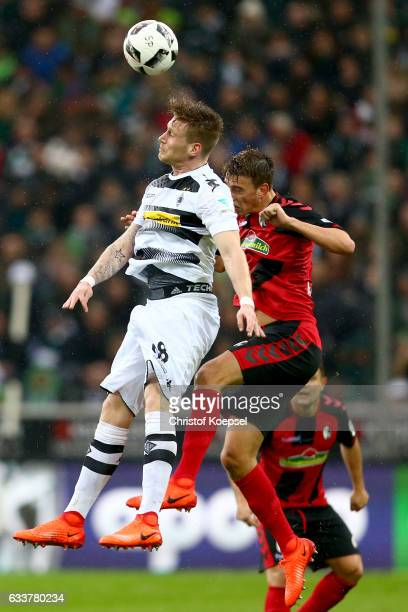 Andre Hahn of Moenchengladbach and Janik Haberer of Freiburg go up for a header during the Bundesliga match between Borussia Moenchengladbach and SC...