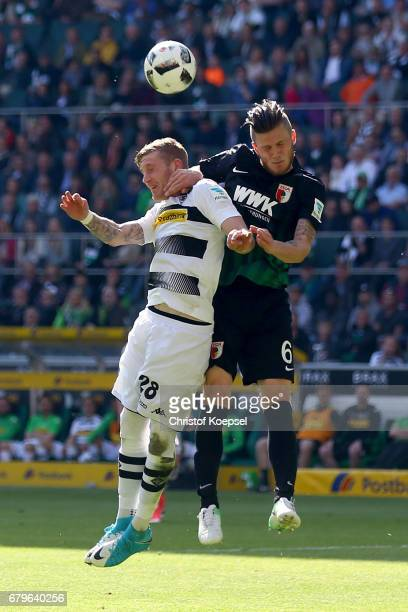 Andre Hahn of Moenchengladbach and Jeffrey Gouweleeuw of Augsburg go up for a header during the Bundesliga match between Borussia Moenchengladbach...