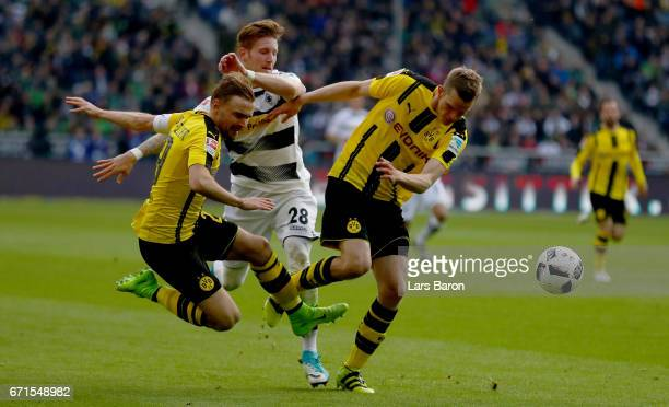 Andre Hahn of Moenchengladbach is challenged by Marcel Schmelzer of Dortmund and Sven Bender of Dortmund during the Bundesliga match between Borussia...