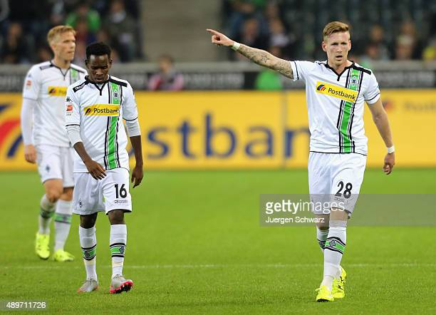 Andre Hahn of Moenchengladbach lifzs his arm beside Ibrahima Traore during the Bundesliga match between Borussia Moenchengladbach and FC Augsburg at...