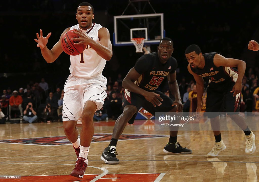 Andre Hollins #1 of the Minnesota Golden Gophers drives by Michael Ojo #50 of the Florida State Seminoles during the NIT Championship semifinals at Madison Square Garden on April 1, 2014 in New York City.