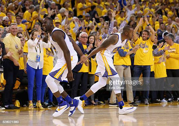 Andre Iguodala and Draymond Green of the Golden State Warriors celebrate in the final minute of their victory over the Portland Trail Blazers in Game...