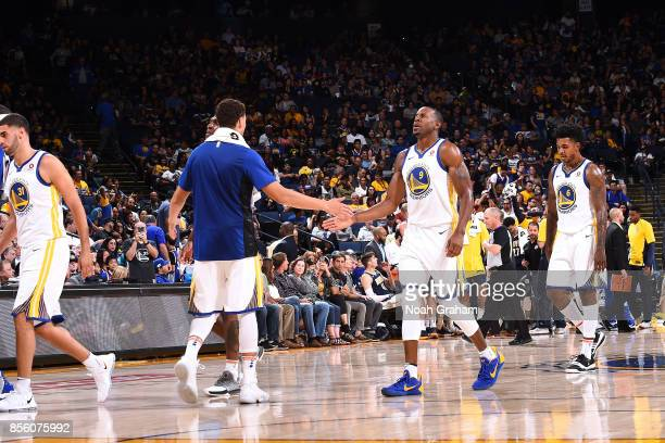 Andre Iguodala and Klay Thompson of the Golden State Warriors high five each other during the game against the Denver Nuggets during a preseason game...