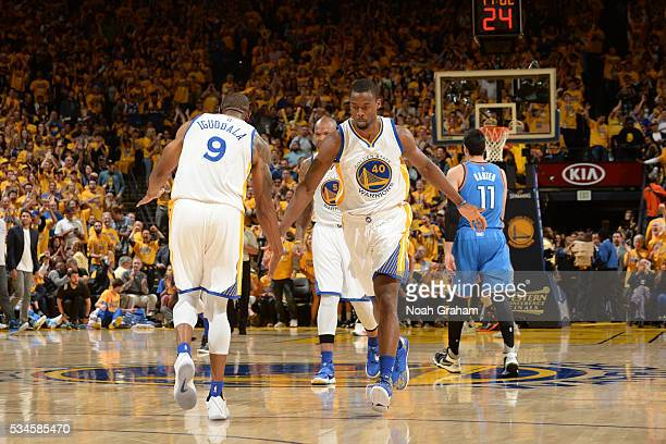 Andre Iguodala high fives teammate Harrison Barnes of the Golden State Warriors against the Oklahoma City Thunder during Game Five of the Western...