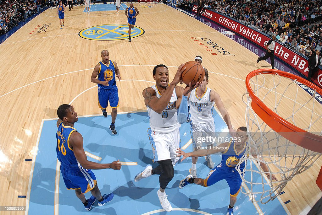 <a gi-track='captionPersonalityLinkClicked' href=/galleries/search?phrase=Andre+Iguodala&family=editorial&specificpeople=201980 ng-click='$event.stopPropagation()'>Andre Iguodala</a> #9 of the Denver Nuggets goes to the basket against <a gi-track='captionPersonalityLinkClicked' href=/galleries/search?phrase=Harrison+Barnes&family=editorial&specificpeople=6893973 ng-click='$event.stopPropagation()'>Harrison Barnes</a> #40 and Stephen Curry #30 of the Golden State Warriors on November 23, 2012 at the Pepsi Center in Denver, Colorado.