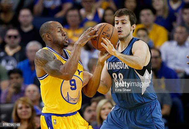 Andre Iguodala of the Golden State Warriors and Nemanja Bjelica of the Minnesota Timberwolves go for a loose ball at ORACLE Arena on April 5 2016 in...