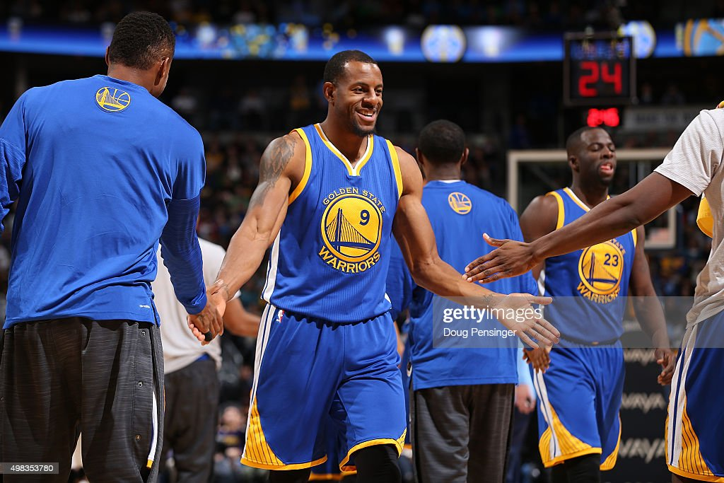 Andre Iguodala of the Golden State Warriors celerbates with teammate as he heads to the bench for a time out against the Denver Nuggets at Pepsi...