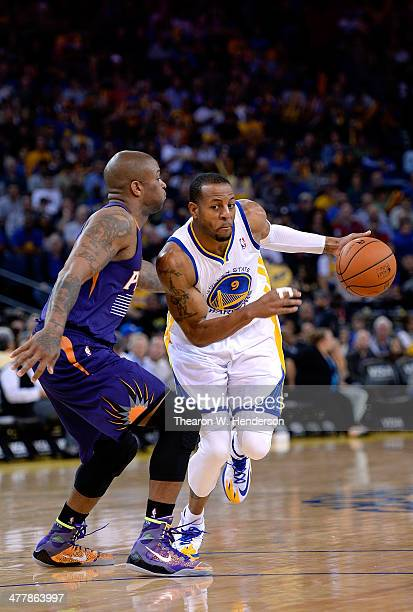 Andre Iguodala of the Golden State Warriors drives on PJ Tucker of the Phoenix Suns at ORACLE Arena on March 9 2014 in Oakland California NOTE TO...