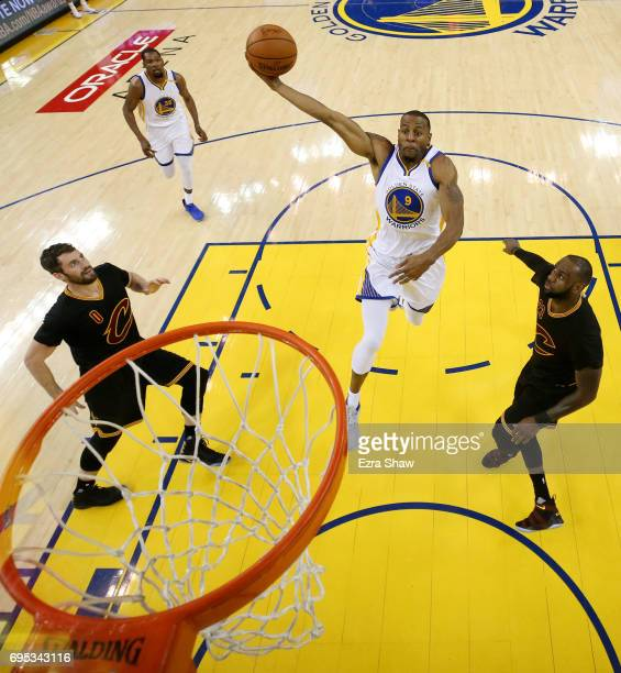Andre Iguodala of the Golden State Warriors dunks the ball past Kevin Love and LeBron James of the Cleveland Cavaliers during the first half in Game...