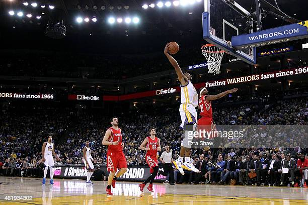 Andre Iguodala of the Golden State Warriors goes up for a dunk against Corey Brewer of the Houston Rockets at ORACLE Arena on January 21 2015 in...