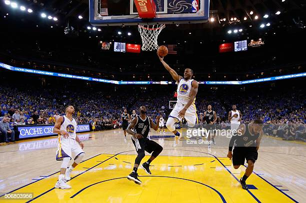 Andre Iguodala of the Golden State Warriors goes up for a shot against Jonathon Simmons and Patty Mills of the San Antonio Spurs at ORACLE Arena on...