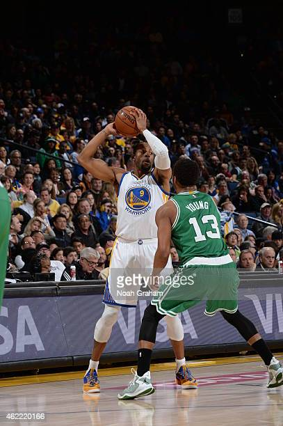 Andre Iguodala of the Golden State Warriors handles the ball against James Young of the Boston Celtics on January 25 2015 at ORACLE Arena in Oakland...