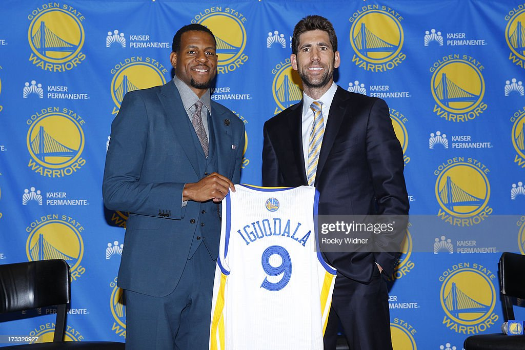 Andre Iguodala #9 of the Golden State Warriors holds up his jersey with General Manager Bob Myers at a press conference on July 11, 2013 in Oakland, California.