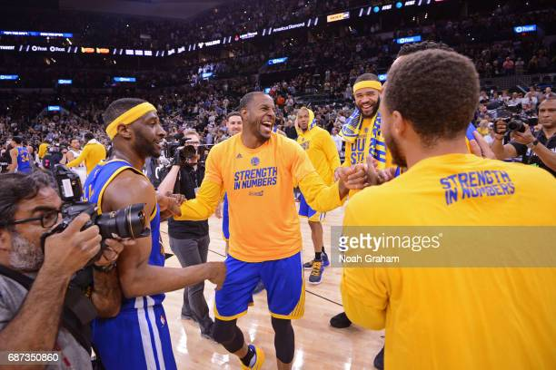 Andre Iguodala of the Golden State Warriors smiles and laughs with teammates on the court after winning Game Four of the Western Conference Finals...