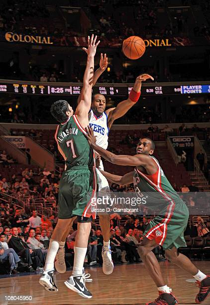Andre Iguodala of the Philadelphia 76ers passes the ball against Ersan Ilyasova and Luc Mbah a Moute of the Milwaukee Bucks during the game on...