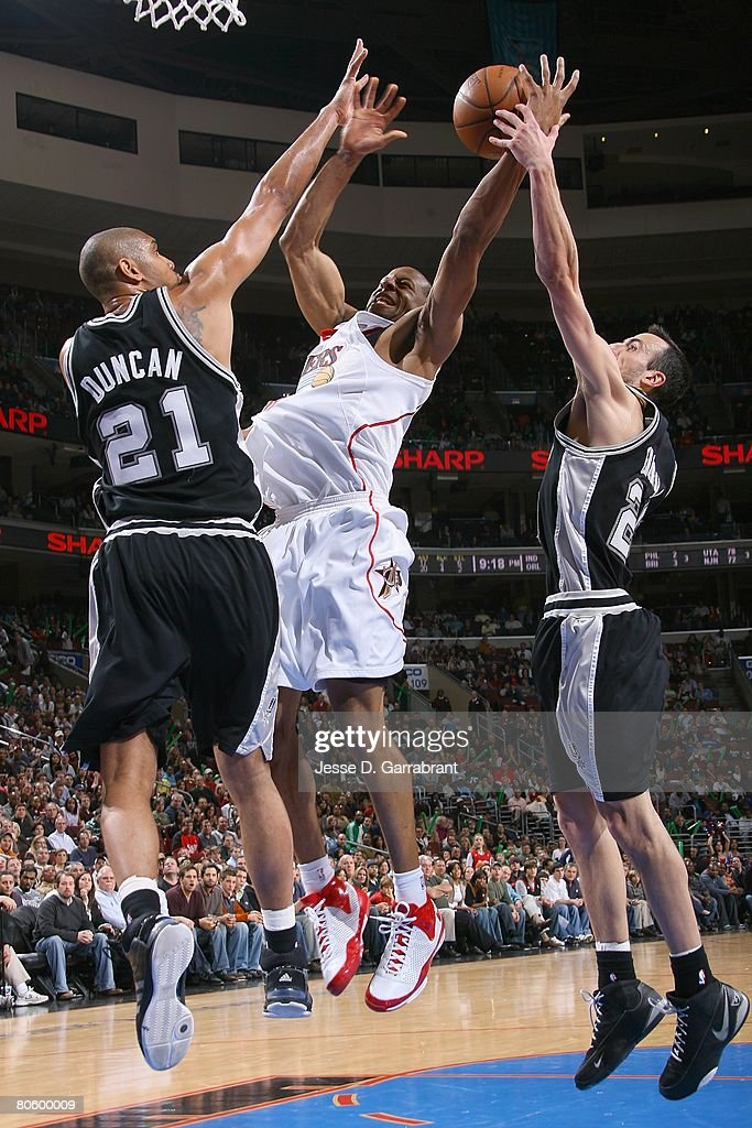 Andre Iguodala #9 of the Philadelphia 76ers takes the ball to the basket against Tim Duncan #21 and Manu Ginobili #20 of the San Antonio Spurs during the game on March 15, 2008 at the Wachovia Center in Philadelphia, Pennsylvania. The Sixers won 103-96.