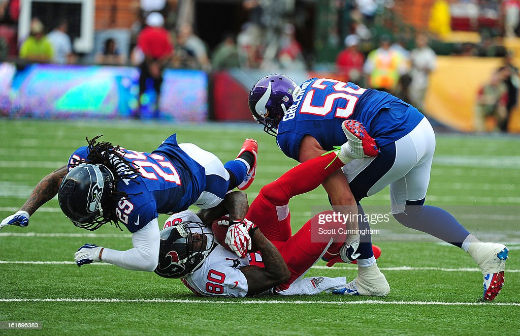 Andre Johnson #80 of the Houston Texans and the AFC is tackled by Earl Thomas #29 and Chad Greenway #52 of the National Football Conference team during the 2013 Pro Bowl at Aloha Stadium on January 27, 2013 in Honolulu, Hawaii