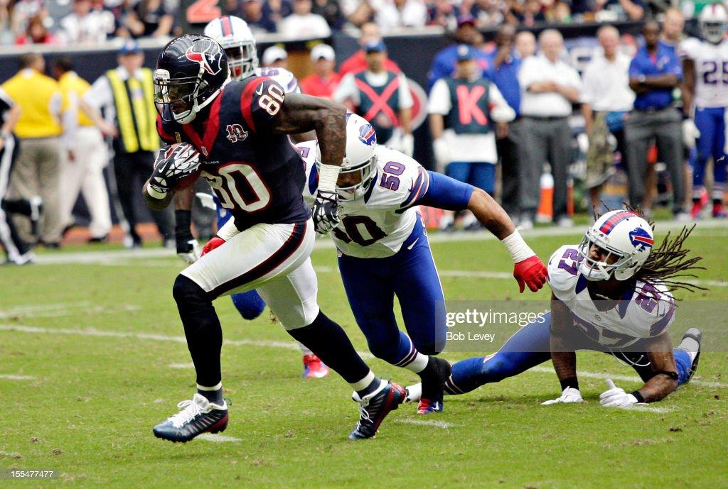 Andre Johnson #80 of the Houston Texans breaks the tackle of Leodis McKelvin #21 of the Buffalo Bills and Nick Barnett #50 of the Buffalo Bills at Reliant Stadium on November 4, 2012 in Houston, Texas. Houston defeated Buffalo 21-9.