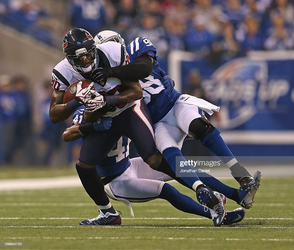 Andre Johnson #80 of the Houston Texans is tackled by Robert Mathis #98 and Antoine Bethea #41 of the Indianapolis Colts at Lucas Oil Stadium on December 30, 2012 in Indianapolis, Indiana. The Colts defeated the Texans 28-16.