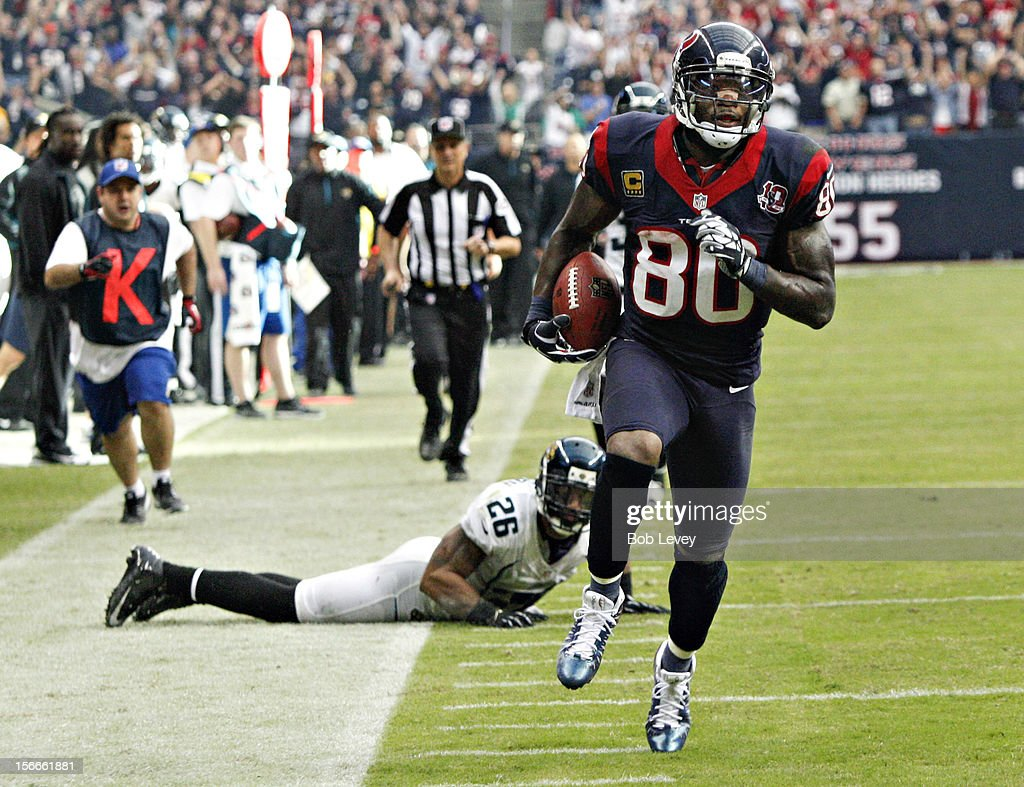 Andre Johnson #80 of the Houston Texans scores on a 48 yard reception in overtime against the Jacksonville Jaguars as Dawan Landry #26 of the Jacksonville Jaguars watches at Reliant Stadium on November 18, 2012 in Houston, Texas. Houston won 43-37 in overtime.