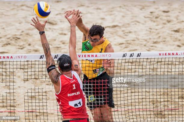 Andre Loyola Stein of Brazil spikes the ball during the gold medal match against Clemens Doppler and Alexander Horst of Austria at FIVB Beach...