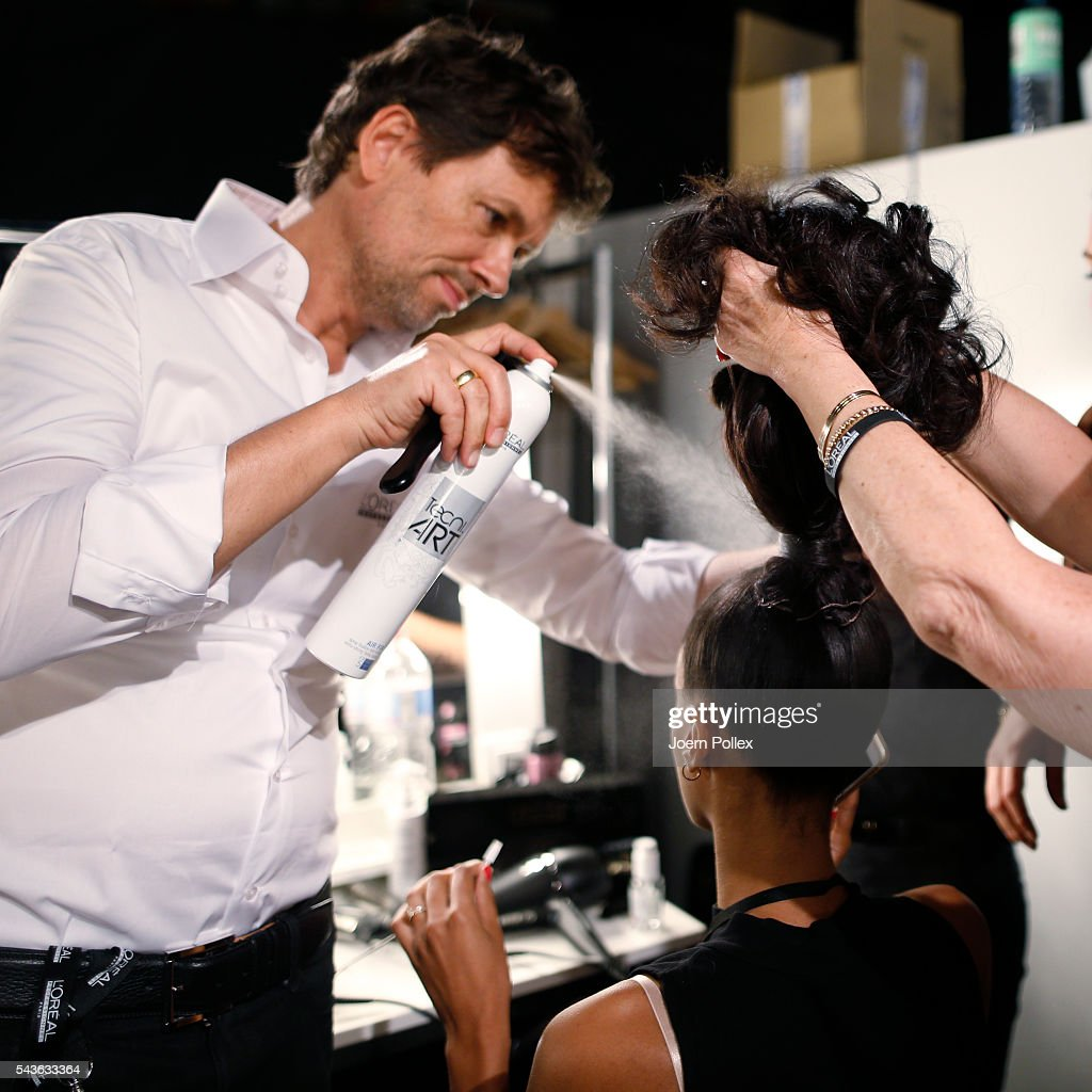 Andre Maertens prepares a model backstage ahead of the Guido Maria Kretschmer show during the Mercedes-Benz Fashion Week Berlin Spring/Summer 2017 at Erika Hess Eisstadion on June 29, 2016 in Berlin, Germany.