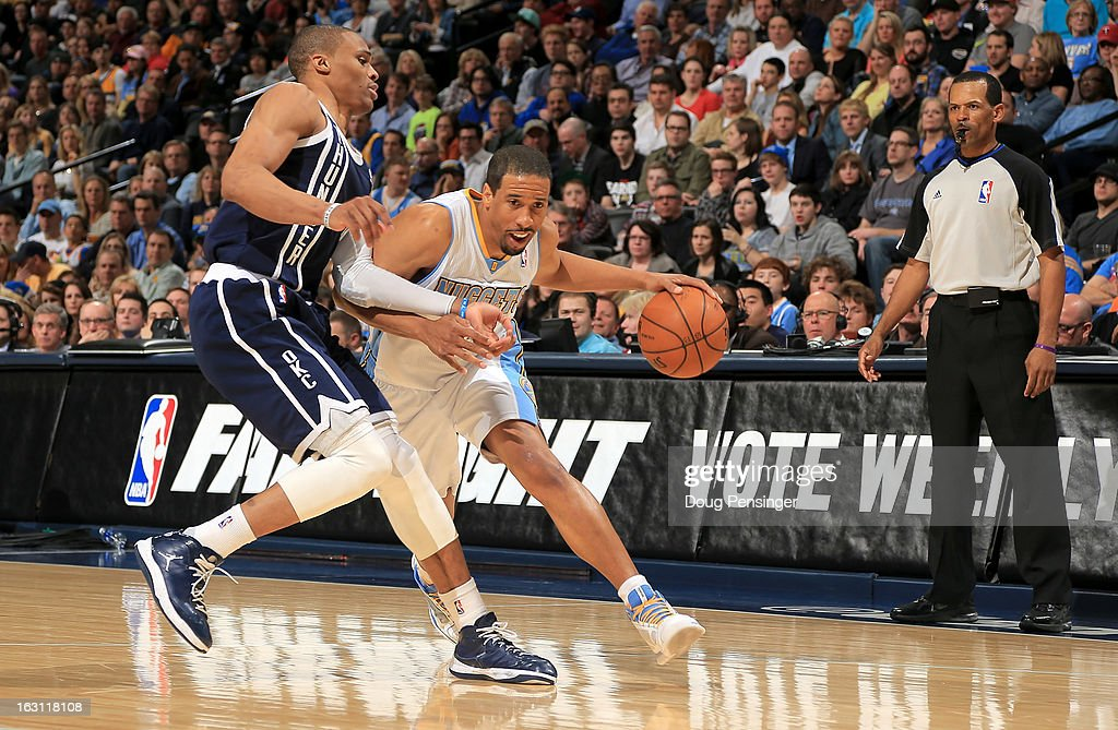 Andre Miller of the Denver Nuggets controls the ball against Russell Westbrook of the Oklahoma City Thunder as referee Eric Lewis oversees the action...