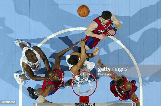 Andre Miller of the Denver Nuggets dishes the ball back out of the key under defensive pressure from Elton Brand Cuttino Mobley and Vladimir...