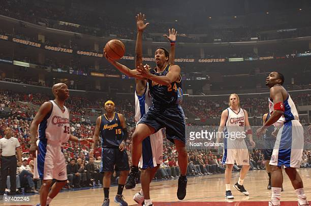 Andre Miller of the Denver Nuggets shoots against Sam Cassell Cuttino Mobley and Chris Kaman of the Los Angeles Clippers in game one of the Western...
