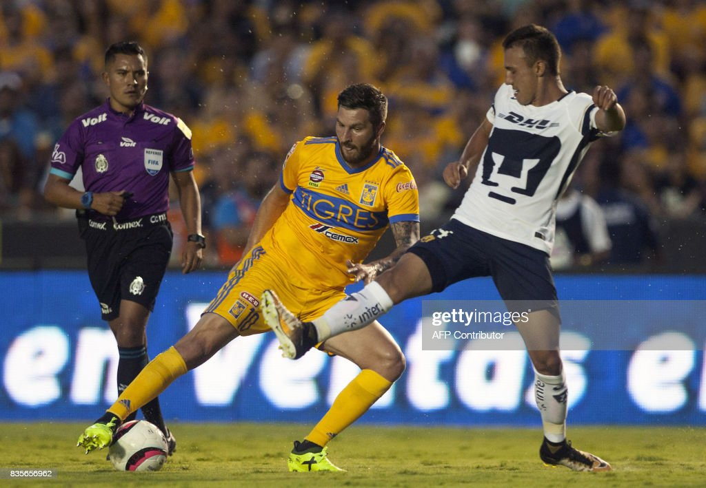 Andre Pierre Gignac (L) of Tigres vies for the ball with Brian Figueroa (R) of Pumas during their Mexican Apertura 2017 tournament football match at the Universitario stadium in Monterrey, Mexico on August 19, 2017. / AFP PHOTO / Julio Cesar AGUILAR