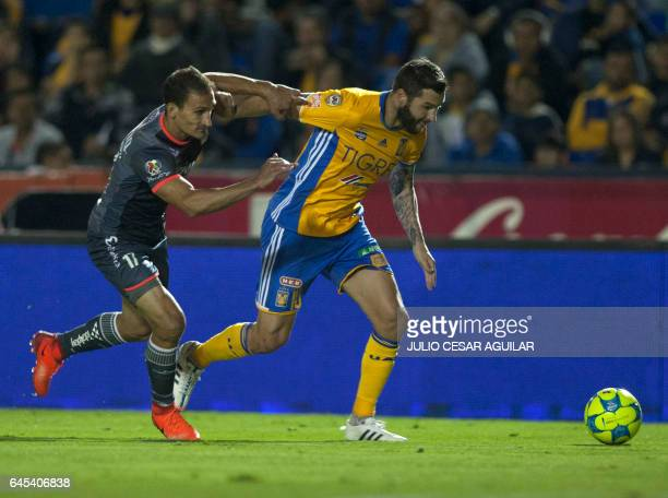 Andre Pierre Gignac of Tigres vies for the ball with Emanuel Loeschbor of Morelia during the Mexican Clausura 2017 tournament football match at the...