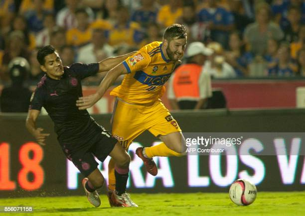 Andre Pierre Gignac of Tigres vies for the ball with Jesus Sanchez of Chivas during their Mexican Apertura football tournament match at the...