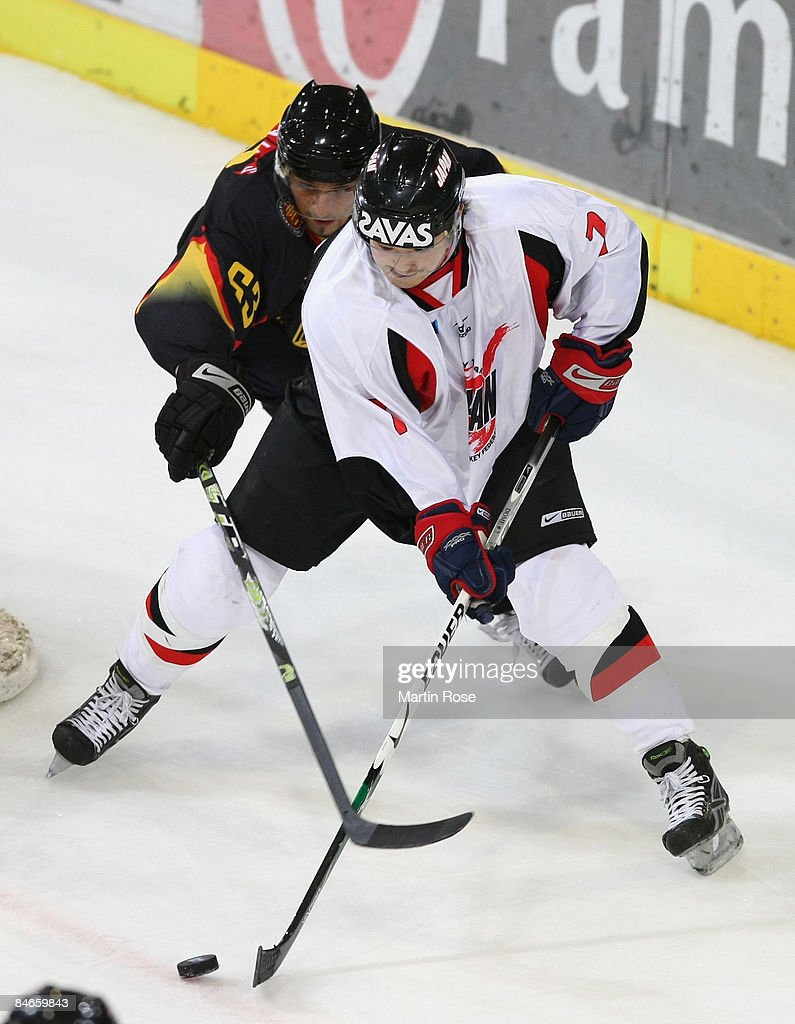 Andre Reiss of Germany and Masato Domeki of Japan battle for the puck during the Vancouver 2010 Qualifier match between Germany and Japan at the TUI...