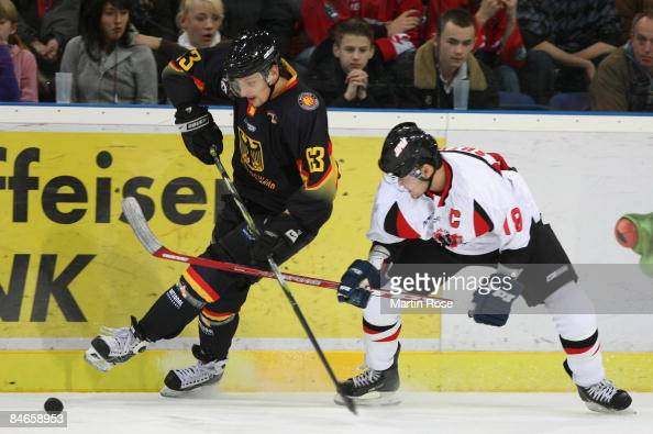 Andre Reiss of Germany and Takahito Suzuki of Japan battle for the puck during the Vancouver 2010 Qualifier match between Germany and Japan at the...