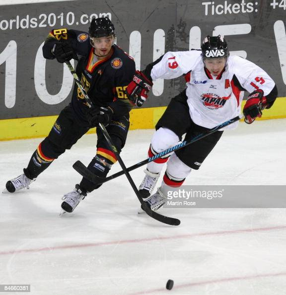 Andre Reiss of Germany and Takeshi Saito of Japan battle for the puck during the Vancouver 2010 Qualifier match between Germany and Japan at the TUI...