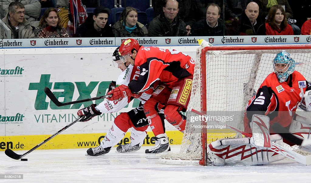 Andre Reiss of Hannover and Alexej Dmitriev of Koelner Haie compete for the puck during the DEL Bundesliga game between Hannover Scorpions and...