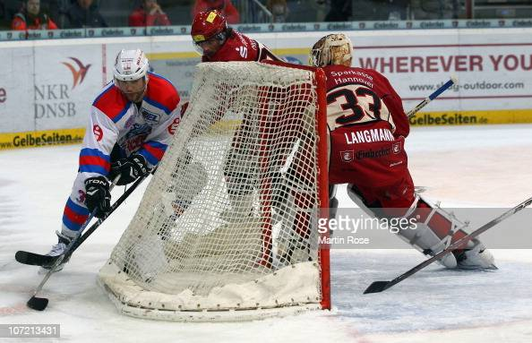 Andre Reiss of Hannover and Brad Leeb of Nuernberg battle for the puck during the DEL match between Hannover Scorpions and Thomas Sabo Ice Tigers at...