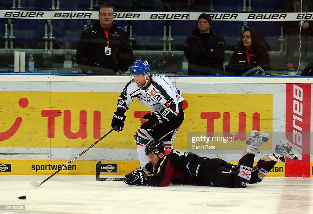Andre Reiss (R) of Hannover and Chad Bassen (L) of Augsburg battle for the puck during the DEL match between Hannover Scorpions and Augsburger Panther at TUI Arena at TUI Arena on January 9, 2013 in Hanover, Germany.