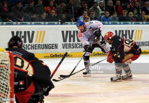 Andre Reiss of Hannover and Connor James of Augsburg battle for the puck during the DEL play off final match between Hannover Scorpions and...