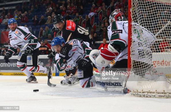 Andre Reiss of Hannover and Daryl Boyle of Augsburg battle for the puck in front of the net during the DEL match between Hannover Scorpions and...