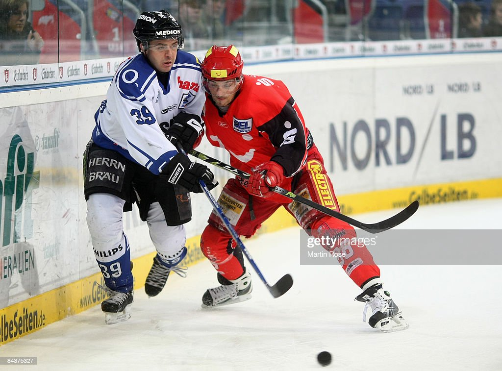 Andre Reiss of Hannover and Thomas Greilinger of Ingolstadt compete for the puck during the DEL Bundesliga game between Hanover Scorpions and ERC...