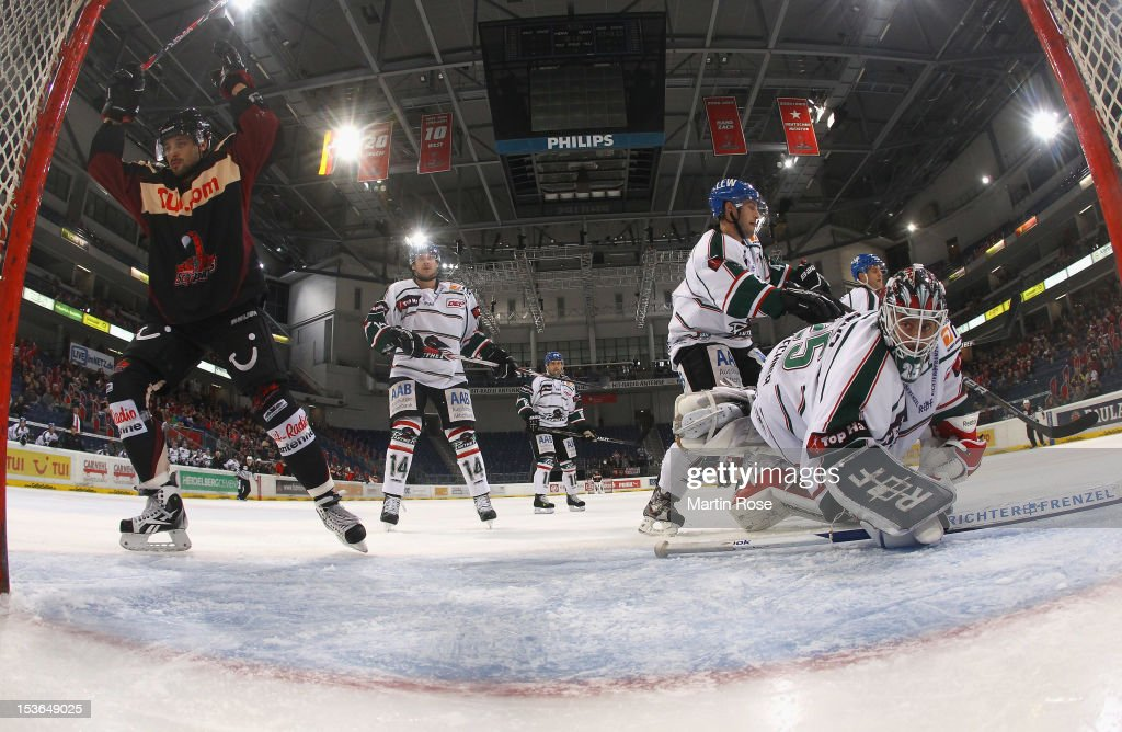 Andre Reiss of Hannover celebrates after he scores his team's 2nd goal over Patrick Ehelechner goaltender of Augsburg during the DEL match between...