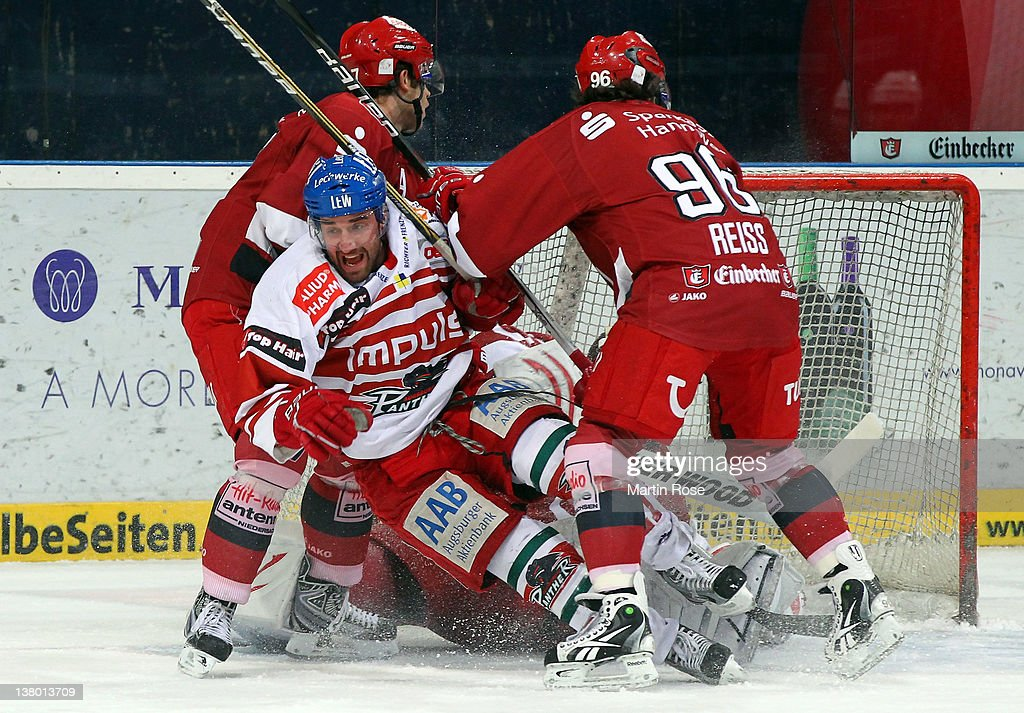Andre Reiss of Hannover checks John Zeller of Augsburg during the DEL match between Hannover Scorpions and Augsburger Panther at TUI Arena on January...