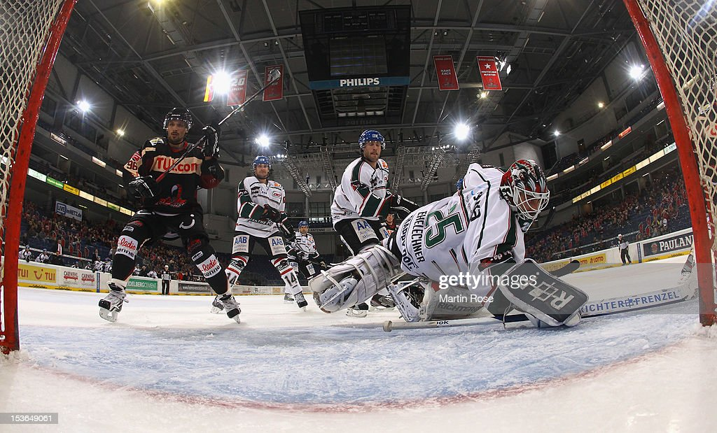Andre Reiss of Hannover scores his team's 2nd goal over Patrick Ehelechner goaltender of Augsburg during the DEL match between Hannover Scorpions and...