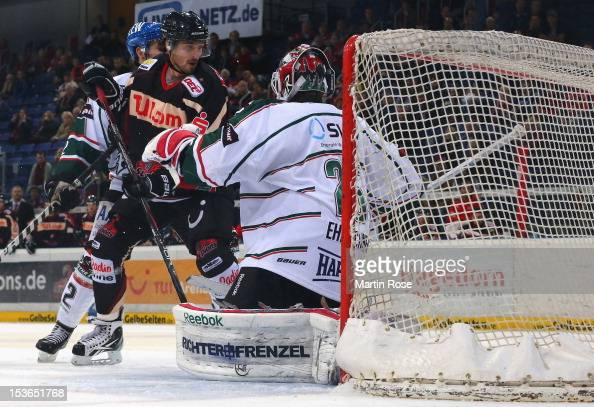 Andre Reiss of Hannover skates in front of Patrick Ehelechner goaltender of Augsburg during the DEL match between Hannover Scorpions and Augsburger...
