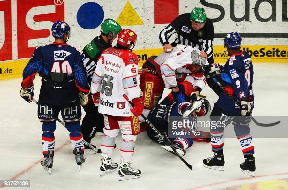 Andre Reiss of Scorpions and Frank Mauer of Adler fight during the Deutsche Eishockey Liga game between Adler Mannheim and Hannover Scorpions at SAP...