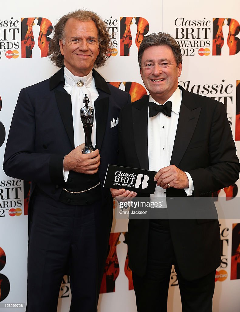 Andre Rieu (L) poses with his Album of the Year trophy after he was presented with it by <a gi-track='captionPersonalityLinkClicked' href=/galleries/search?phrase=Alan+Titchmarsh&family=editorial&specificpeople=178200 ng-click='$event.stopPropagation()'>Alan Titchmarsh</a> (R) as they attend the Classic BRIT Awards at the Royal Albert Hall on October 2, 2012 in London, England.