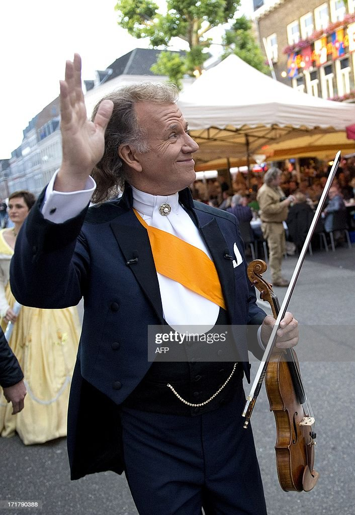 Andre Rieu waves to people prior to his first concert at the Vrijthof square in central Maastricht, on June 28, 2013. The world famous violinist and conductor will give 8 concerts between June 28 and July 14. netherlands out